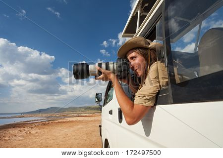 Female safari tourist taking photos from the open window of jeep on game drive in Nakuru