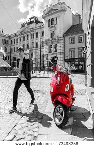 VILNIUS LITHUANIA - APRIL 27 2016: Red scooter standing on the street in black and white background of Vilnius old town Lithuania