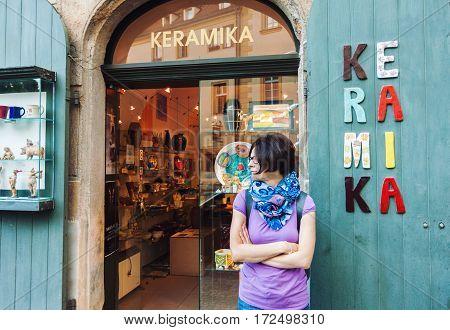 PRAGUE CZECH REPUBLIC - JUNE 27 2016: Young woman standing in front of ceramics shop entrance in Prague Czech Republic