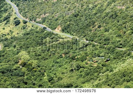 Rural Asphalt Road Winding Through Green Valley