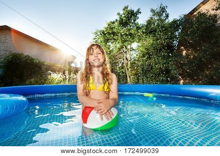Happy beautiful girl playing with sand ball in the swimming pool at sunny day