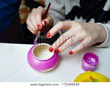 The girl paints and a clay pot