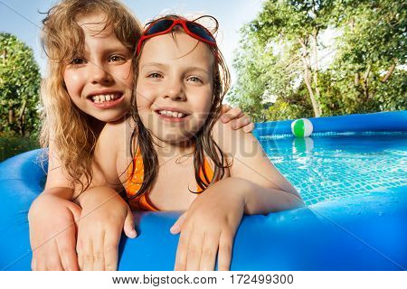 Close-up portrait of two ten years old girls posing in the swimming pool in summer