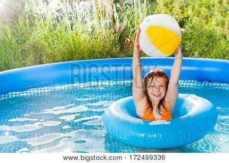 Happy ten years old girl playing with wind ball holding it overhead, standing in the inflatable pool
