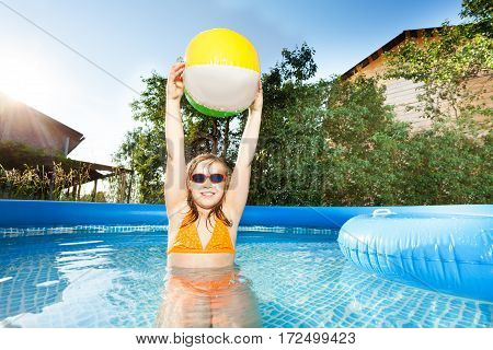 Portrait of ten years old girl playing with multicolored beach ball holding it overhead in swimming pool