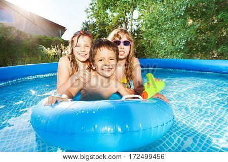 Portrait of happy kids, boy and two girls, swimming in the inflatable pool with blue rubber ring at sunny day