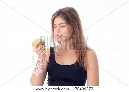 Beautiful athletic girl standing sideways holding an apple in his hand and looking at him