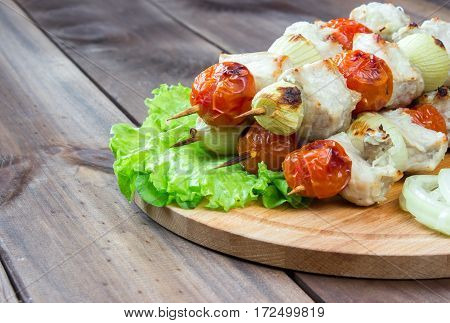 Skewered on wooden sticks tasty pork meat and vegetables mix, on wooden background. space for text