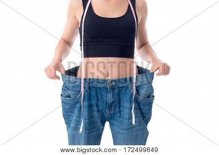 slender girl stands in huge denim pants close-up in studio