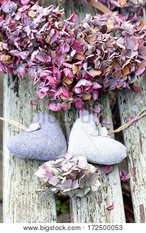 Two tweed hearts with a hydrangea wreath on a shabby chic bench