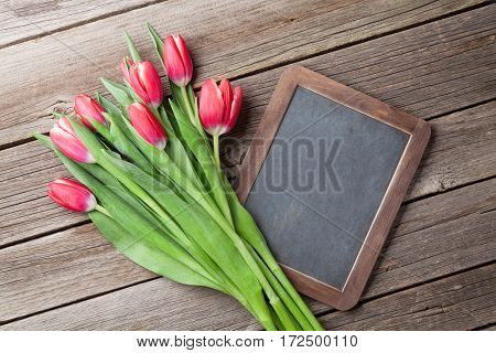 Red tulips bouquet and chalkboard on wooden background. Top view with space for your greetings