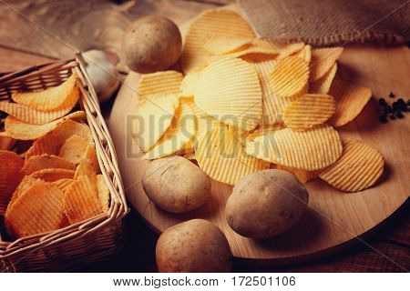 Crispy potato chips and potato on a wooden cutting board