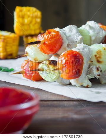 Skewered on wooden sticks tasty pork meat and vegetables mix, on wooden background. vertical