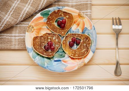 Fritters with cranberry, metal fork and tablecloth