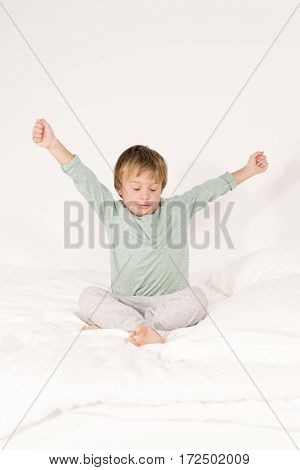 A boy lies on a bed and stretches