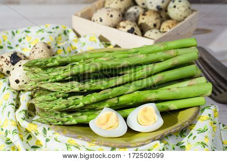 Spring season dish - fresh green asparagus and quail eggs on wooden table