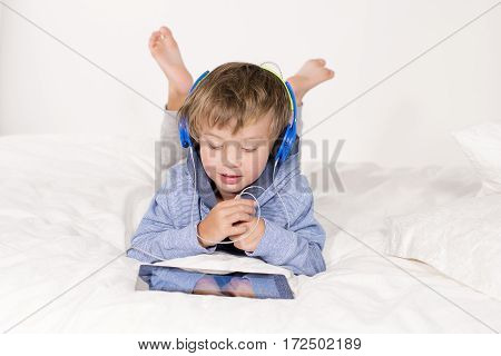 Ein Junge Liegt Mit Notebook Und Kopfhörer Auf Einem Bett