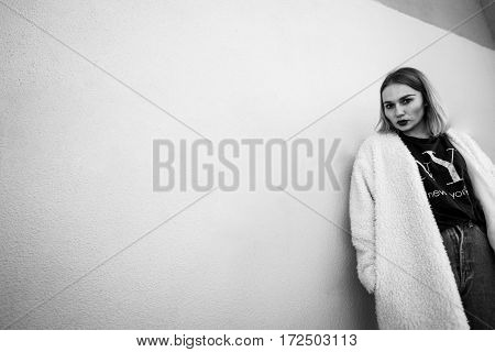 Black And White Portrait Of A Stylish Woman Posing Against A Grey Background While Lying Against The
