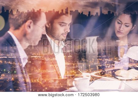 High angle view of illuminated cityscape against group of businesspeople looking at document
