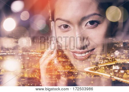 High angle view of illuminated cityscape against businesswoman talking on mobile phone