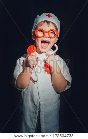 Child dressed doctor on a dark background. isolated