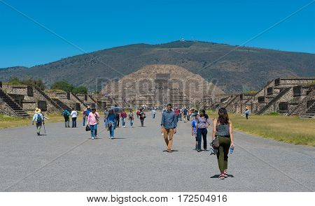 San Juan Teotihuacan Mexico - Octobar 13 2016: Tourists walking along the Avenue of the Dead visiting the Pyramid of the Moon in San Juan Teotihuacan near Mexico City Mexico.