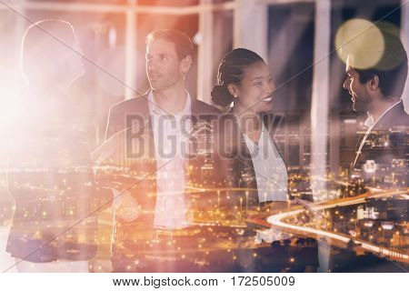 High angle view of illuminated cityscape against group of businesspeople shaking hands with each other
