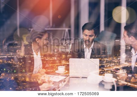 High angle view of illuminated cityscape against group of businesspeople interacting with each other in meeting