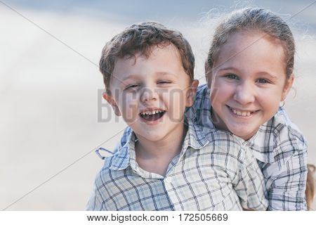 Portrait Of Happy Children Near A House At The Day Time.