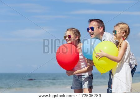 Father and children standing on the beach at the day time. Concept of happy friendly family.