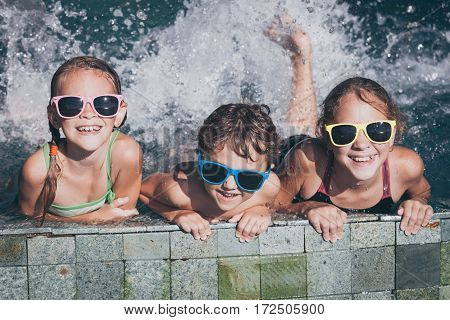 Three Happy Children  Playing On The Swimming Pool At The Day Time.
