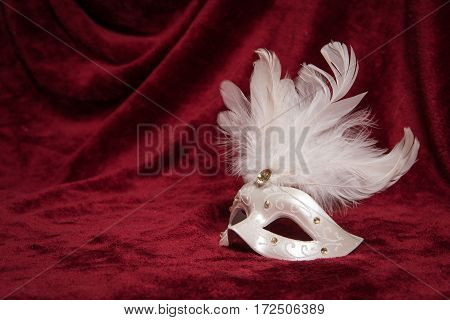 White venetian carnival mask with white feathers seen from the side on a draped red velvet theater curtain