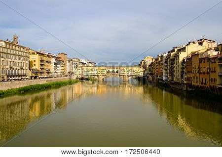 View of medieval stone bridge Ponte Vecchio and the Arno River from the Ponte Santa Trinita (Holy Trinity Bridge) in Florence, Tuscany, Italy.