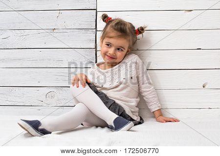 Little Cute Girl School Girl Sitting On White Wooden Background