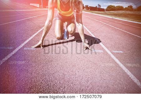 Female athlete ready to run on running track on sunny day