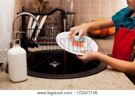 Child washing a plate with sponge at the kitchen sink - closeup, shallow depth