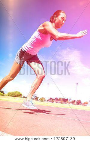 Female athlete running on running track on sunny day