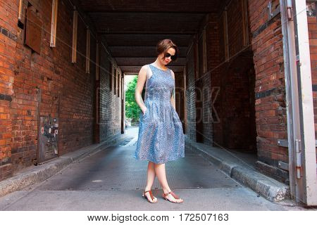 Young beautiful woman walking outside.  Caucasian woman wearing sundress walking in the city and enjoy her summer vacation