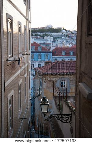Old narrow street of Lisbon, Portugal, evening light at sunset