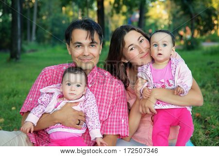 Happy young family with infant twins - baby sisters resting outdoors
