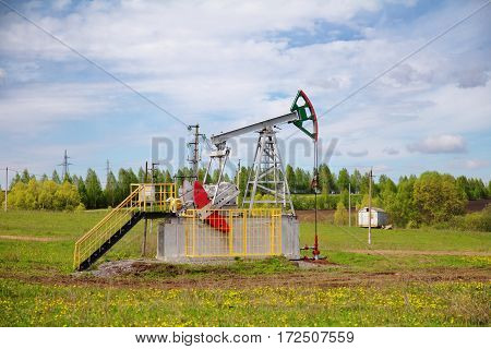 Pump jack in the beautiful summer field.