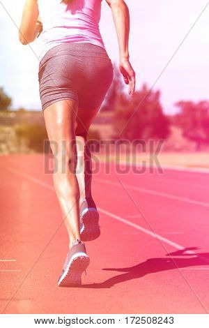 Rear view of female athlete running on running track on sunny day