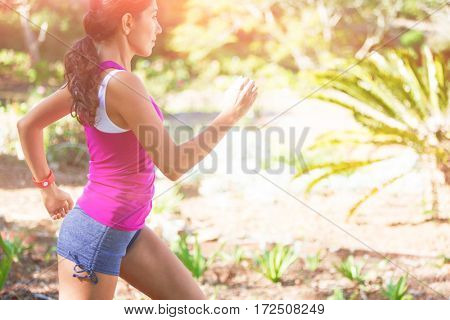 Woman exercising in park on sunny day