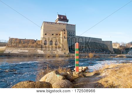 NARVA, ESTONIA - JANUARY 3, 2017: Hermann Castle Museum near The Narva (Narova) River which is the border between Estonia and Russia. Foreground is a boundary post in Russian town Ivangorod