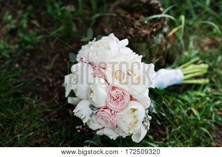Elegance Wedding Bouquet Of White And Rose Peonies With Wedding Rings At Green Grass.