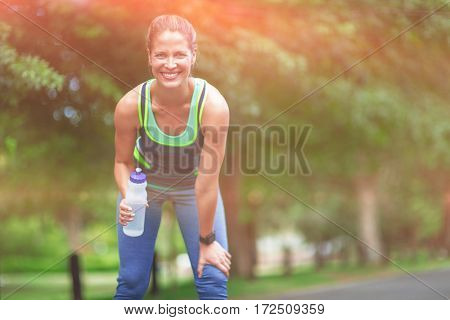 Marathon female athlet drinking water in park