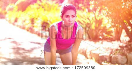 Tired beautiful woman taking break while jogging in park