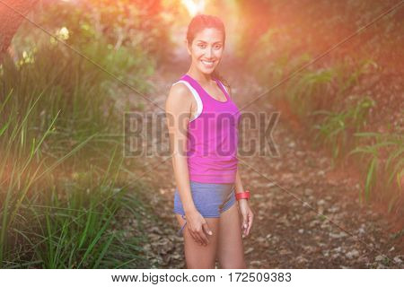 Smiling fit woman standing on field
