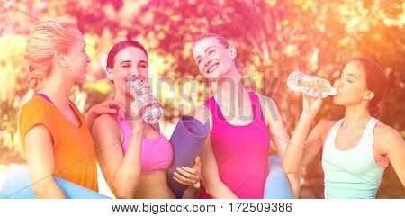 Beautiful women holding exercise mat after workout in park