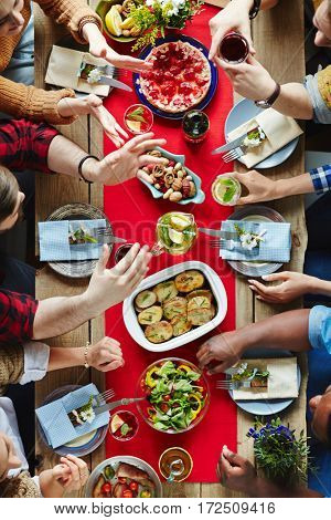 Group of friends talking by served festive table